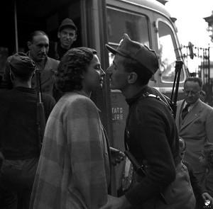 11. Un casto bacio alla partenza per il fronte, sotto lo sguardo del ministro della propaganda di Salò, Ferdinando Mezzasoma, 16 ottobre 1944 © Istituto Luce - Cinecittà