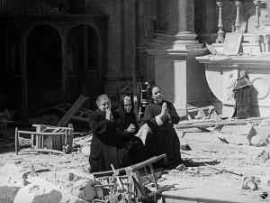 14. Donne pregano tra le rovine della chiesa di Sant'Anna, Cagliari, febbraio 1943 © Istituto Luce - Cinecittà